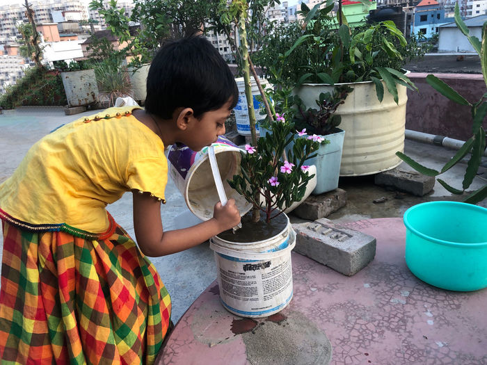 Side view of boy holding flower pot