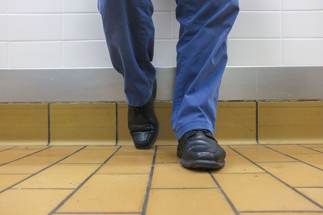 View of the lower legs of a dressed man, waiting against a wall. Patiently Waiting Waiting Casual Clothing Indoors  Lifestyles Men Men Shoes One Person Patience Real People Shoe Standing Tile Tiled Floor
