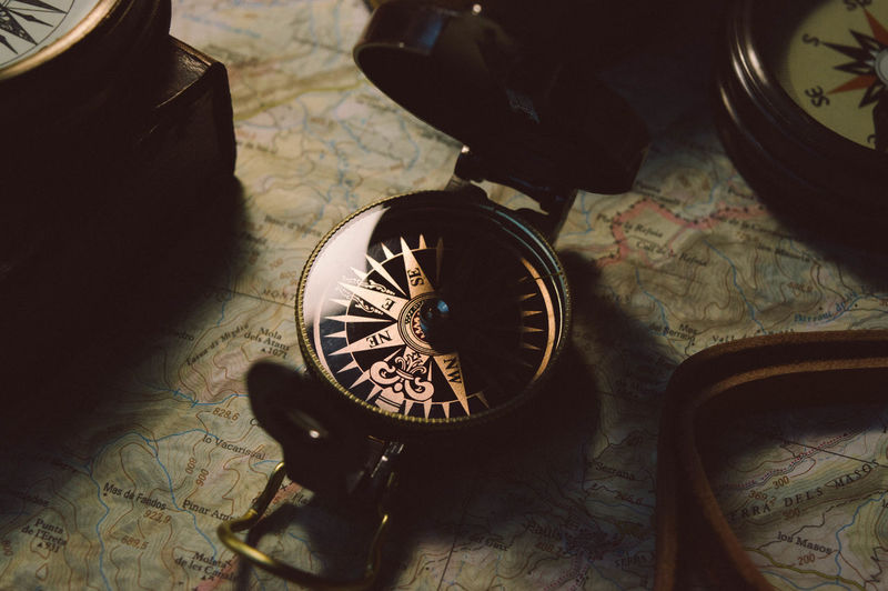 Close-up of navigational compass on map