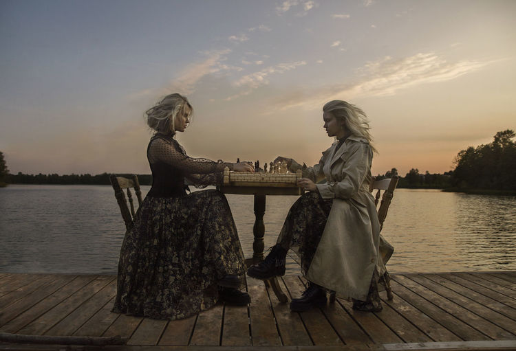 Side view of women sitting on pier against sky during sunset