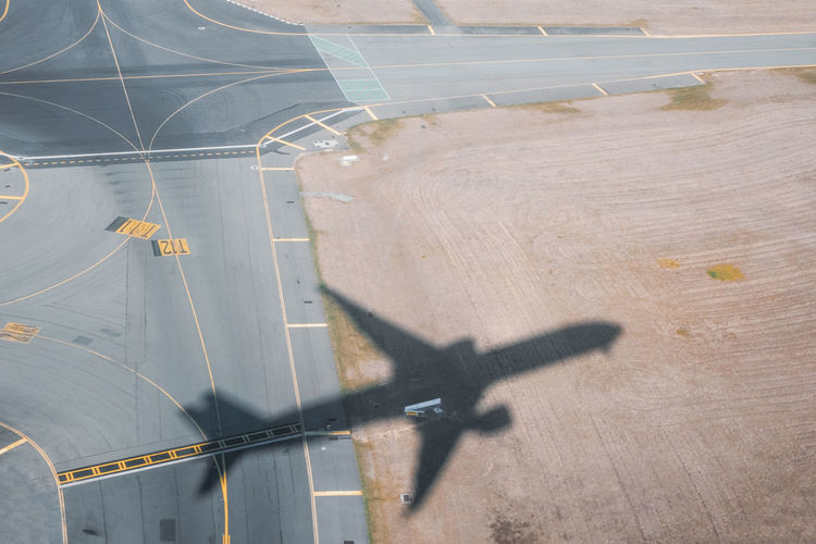 Aerial View Aerospace Industry Air Vehicle Airplane Airport Airport Runway Day Flight Flying High Angle View Leaving Marking Mode Of Transportation Nature No People Outdoors Road Road Marking Shadow Sign Sunlight Symbol Taking Off Transportation Travel