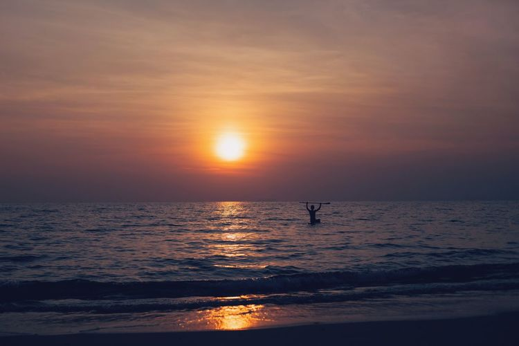 Silhouette person on sea against sky during sunset