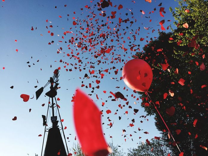 Low angle view of red confetti and balloon against sky