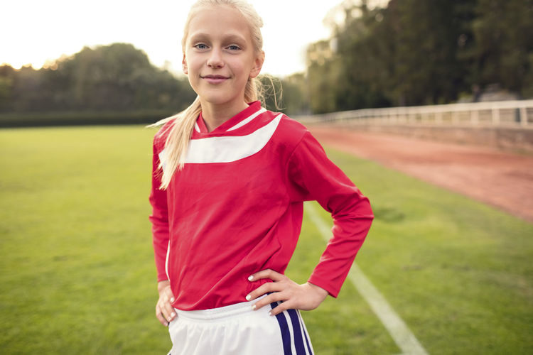 Portrait of smiling girl standing on field