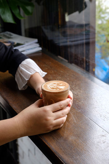 Copped hands of woman holding coffee cup on table in cafe