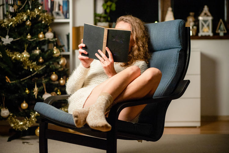 Full length of woman reading book while sitting on chair at home
