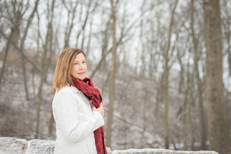 Portrait of woman standing against bare trees during snowfall