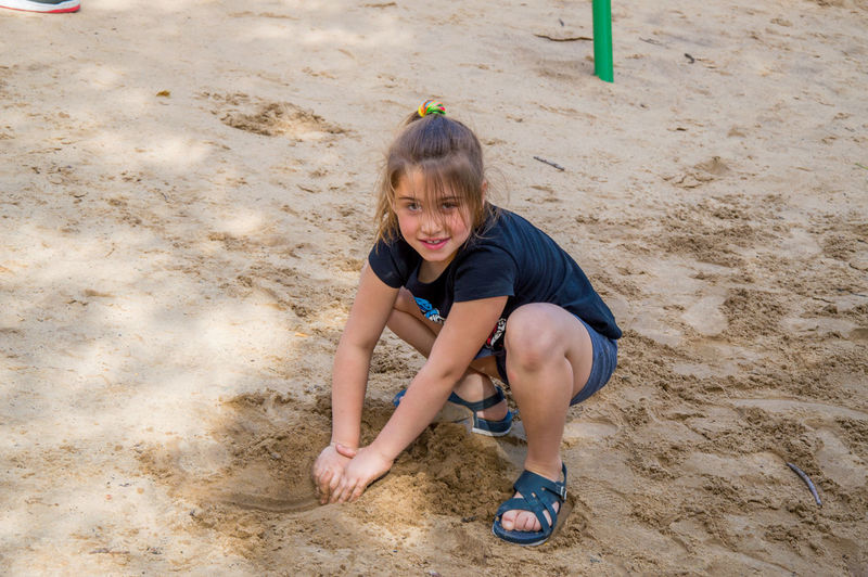 Portrait Of Smiling Girl Playing On Sandy Beach
