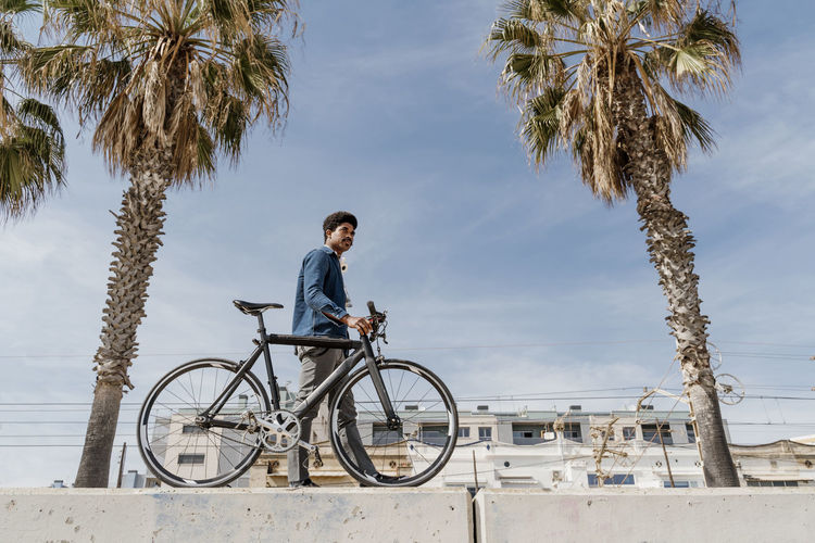 Man riding bicycle on palm trees