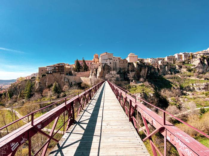 Footbridge over mountain against blue sky