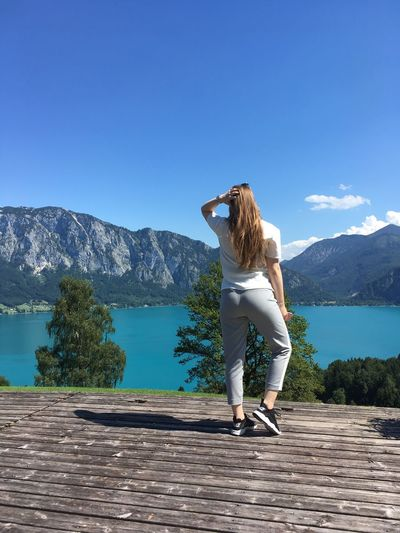 Mountain One Person Rear View Mountain Range Day Water Nature Beauty In Nature Casual Clothing Real People Blue Lake Clear Sky Outdoors Tranquil Scene Standing Lifestyles
