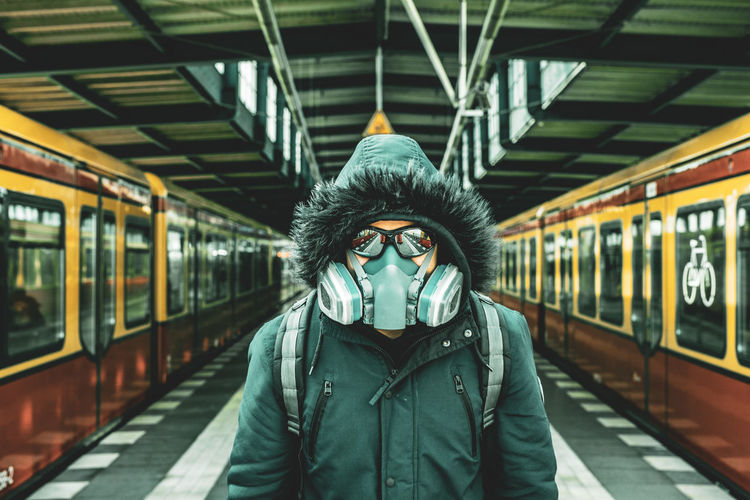 Portrait of man wearing mask standing at railroad station platform