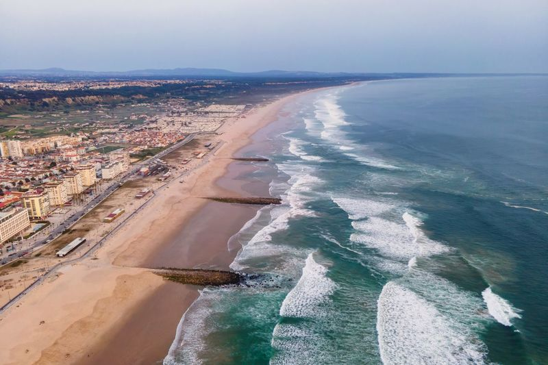 Aerial view of costa da caparica landscape at sunset, view of the majestic beach, setubal, portugal.