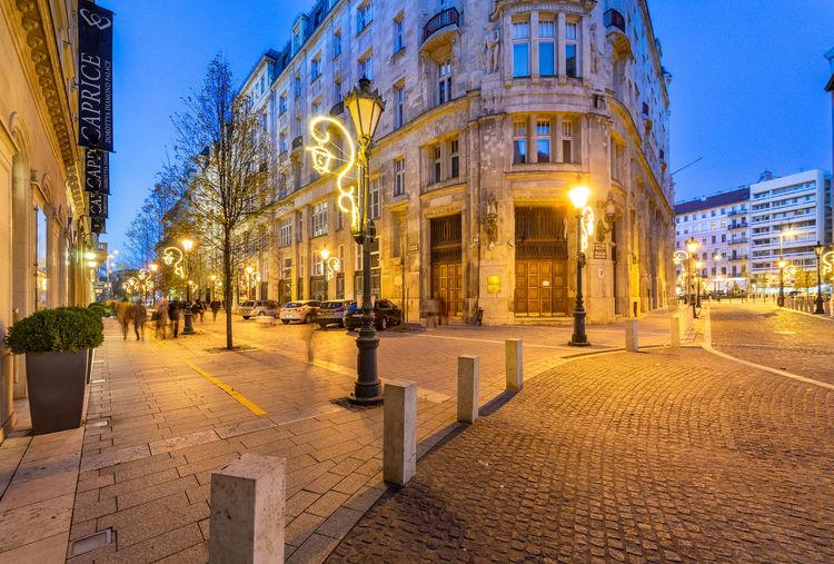 Street lights on sidewalk against buildings at night