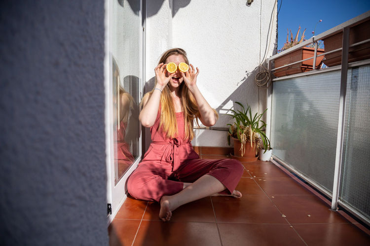 Woman sitting on potted plant against wall