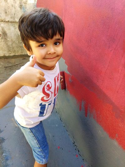 Portrait of boy gesturing thumbs up while standing against wall