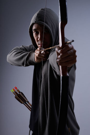 Man with arrow on grey background Arrow Adult Adults Only Close-up Day Front View Holding Hood - Clothing One Man Only One Person One Young Man Only Only Men People Standing Studio Shot Weapon Young Adult