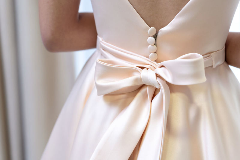 Close up wedding dress ribbon Wedding Celebration Bride White Color Newlywed Event Midsection One Person Standing Ribbon - Sewing Item Life Events Adult Wedding Dress Ribbon Focus On Foreground Real People Women Tied Up Indoors  Wedding Ceremony Fashion