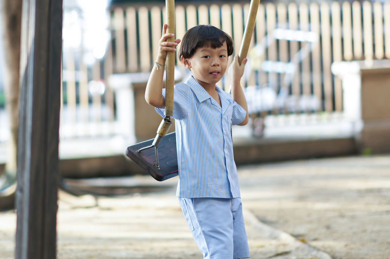 Cute boy holding swing while standing outdoors in playground
