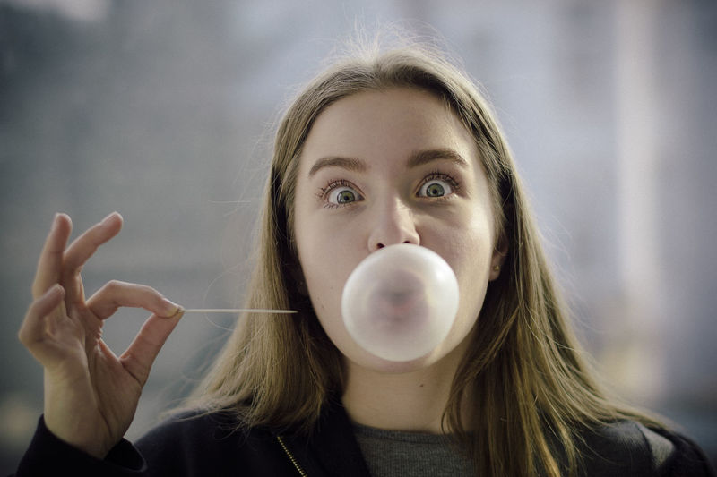 Close-Up Portrait Of Beautiful Young Woman Blowing Bubble Gum And Holding Toothpick