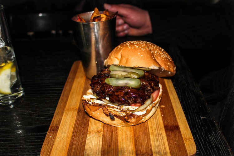 Cropped Image Of Person With Burger At Restaurant