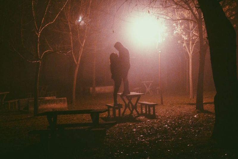 Couple standing on picnic table at park during night