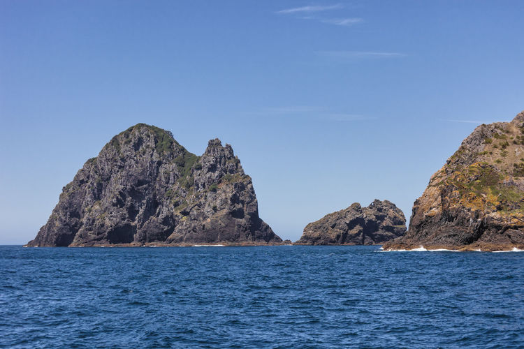 Rock Formations In Sea Against Blue Sky