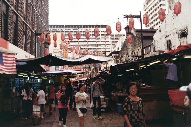 People in market against sky in city