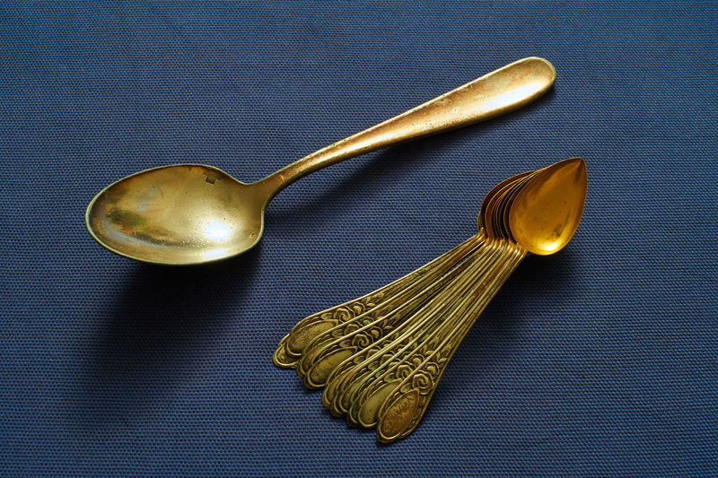 High angle view of golden spoons on table