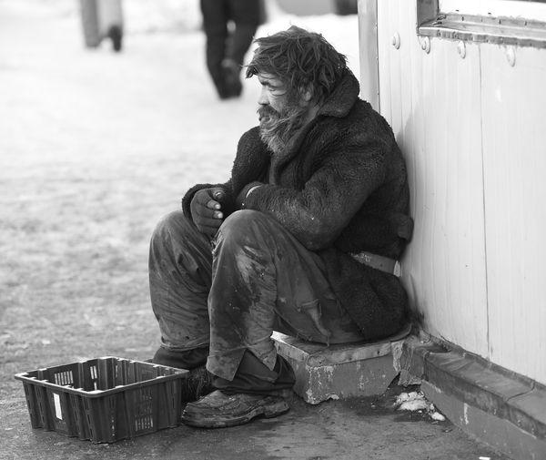 Rear view of man sitting on street