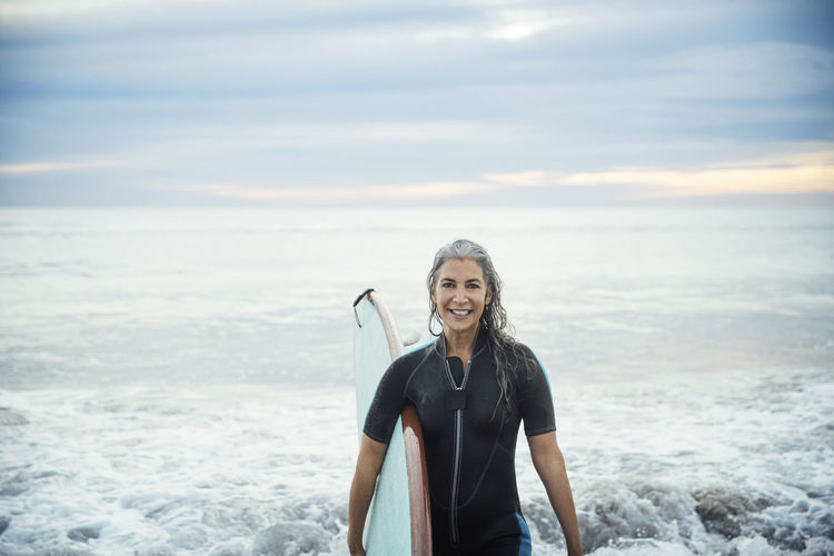 Portrait of happy wet female surfer carrying surfboard at delray beach