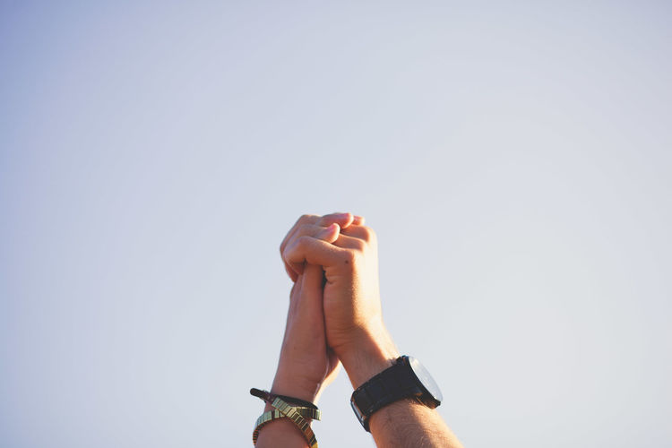 Couple holding hands against clear sky