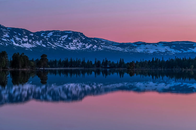 Scenic view of lake by snowcapped mountains against sky during sunset