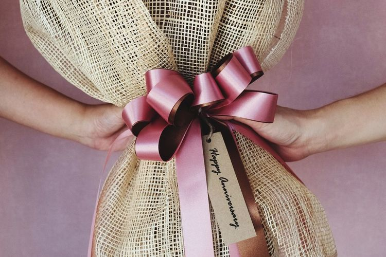 Cropped hands of people holding tied gift