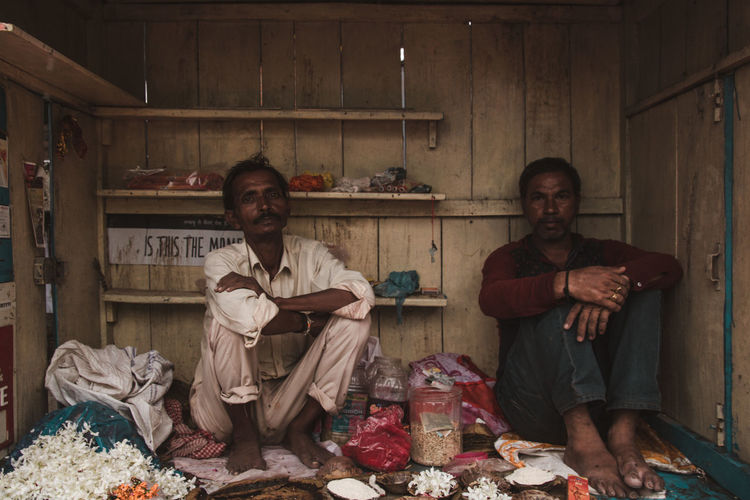 Portrait of young men sitting at their shop