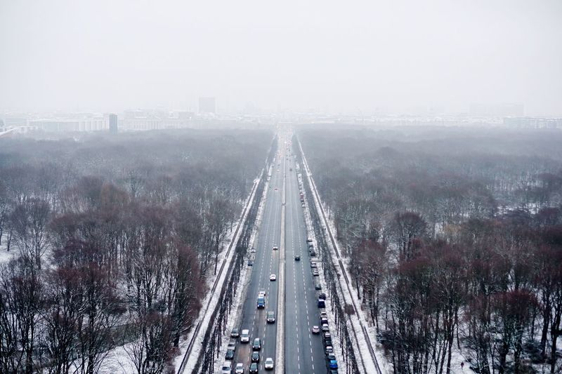 High angle view of road amidst trees against sky during winter