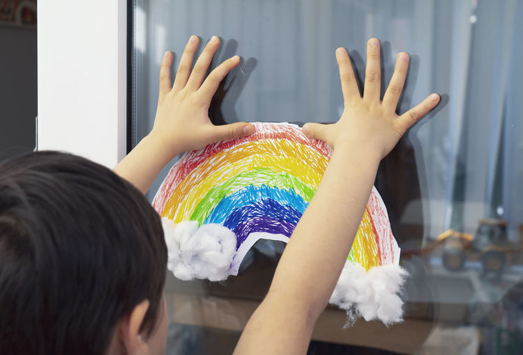 Rear view of boy sticking rainbow drawing on glass