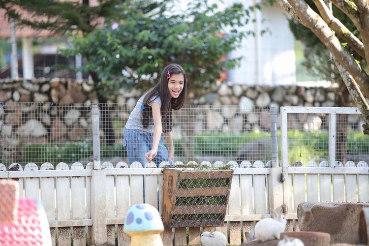 Cute girl standing by fence feeding rabbit