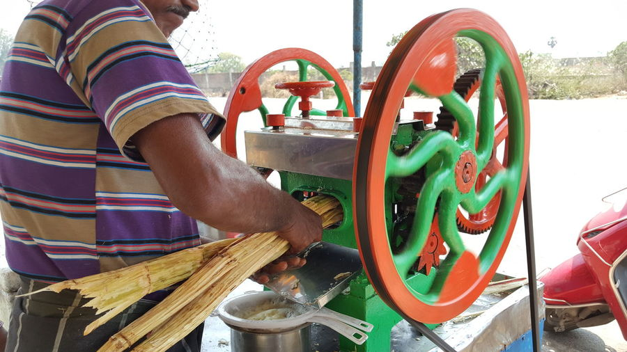 Midsection of vendor crushing sugar canes in machinery at market stall