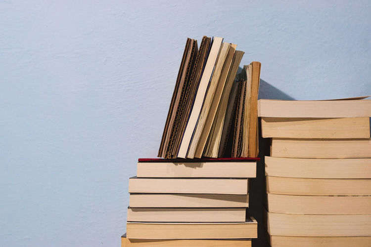 Stack of books on table against wall