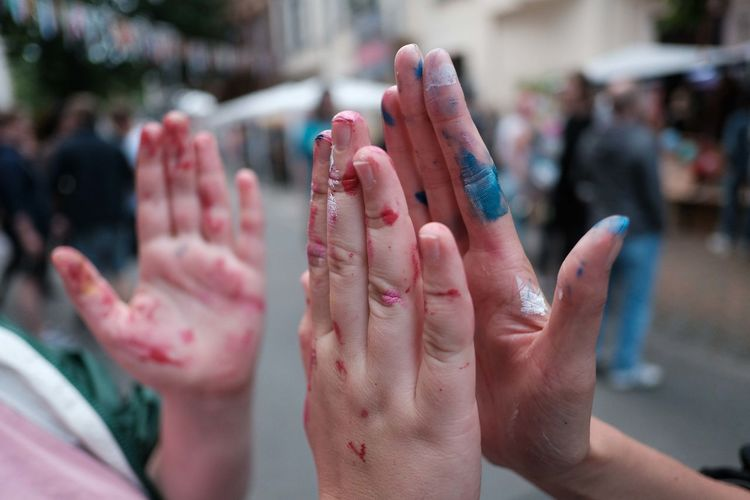 Cropped hands of messy friends high-fiving on footpath in city