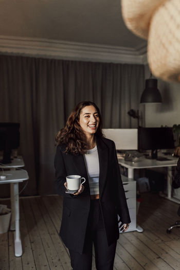 Portrait of a smiling young woman with coffee cup