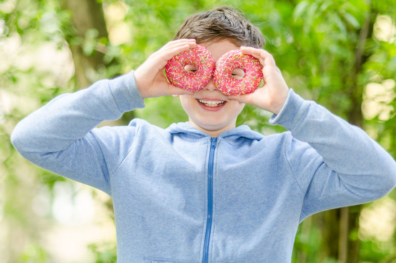 Portrait of smiling boy looking through donuts