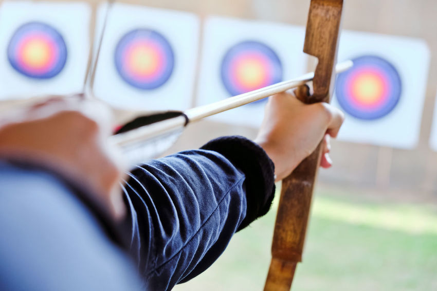 Archer holds his bow aiming at a target Arrow Bow Archer Archery Archery Bows Archery Competition Archery Target Close-up Holding Human Hand One Person People Skill  Sport Sports Photography