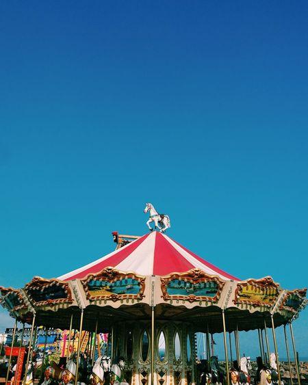 People at amusement park against clear blue sky