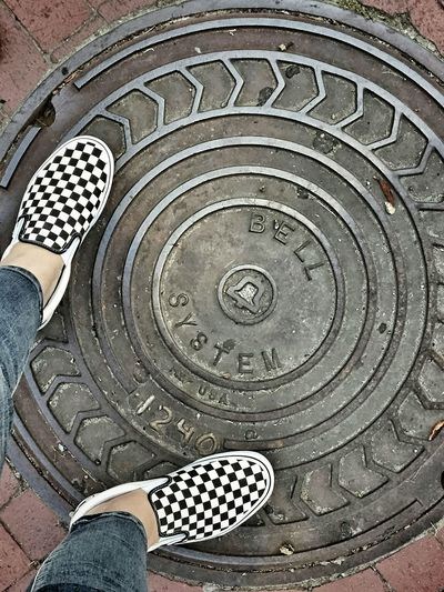 Brick Metal Bell Writing Print Numbers City Street Walking Around Standing Patterns Low Section Concentric Pattern Shoe Close-up Manhole  Lid Footwear Human Foot Sewer Gutter Canvas Shoe Feet