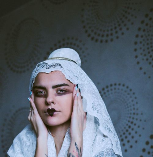 Portrait of young woman with make-up wearing headscarf