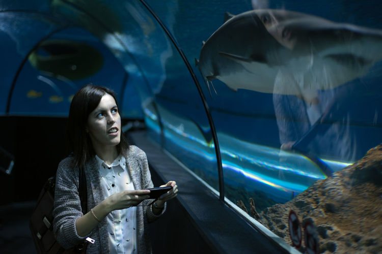 Young woman looking at fish in aquarium