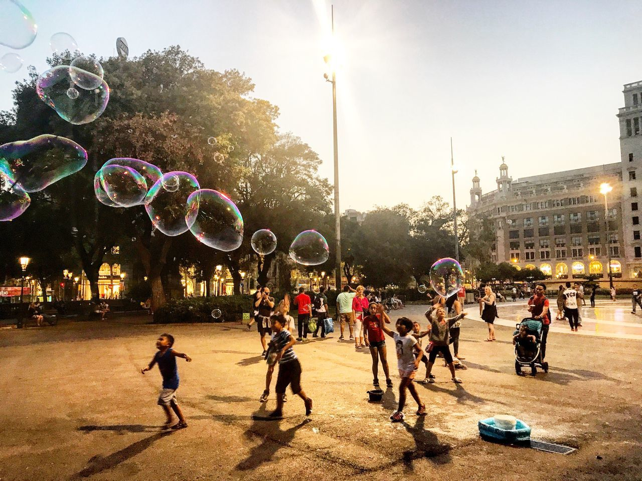 bubble, bubble wand, large group of people, mid-air, fun, playing, sunlight, enjoyment, motion, building exterior, leisure activity, outdoors, childhood, real people, tree, day, architecture, fragility, nature, sky, people, adult