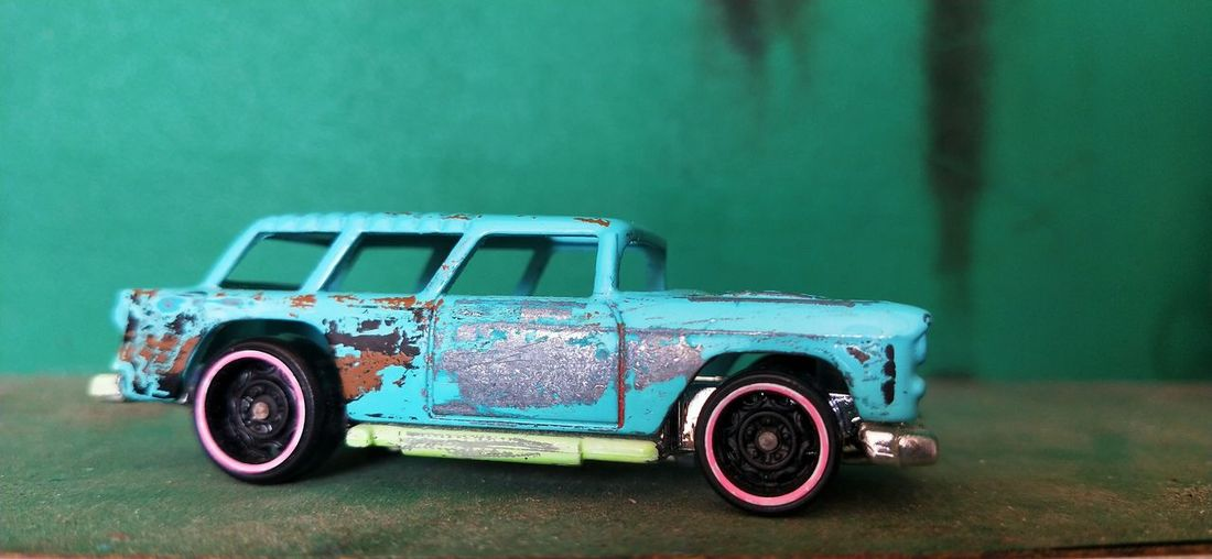 Toy car against blue wall